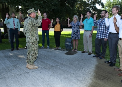 PANAMA CITY, Florida - Naval Surface Warfare Center Panama City Division Commanding Officer Capt. Aaron Peters, USN, administers the oath of office to 11 newly hired federal civil service employees at the flagpole Aug. 6, 2018. U.S. Navy photos by Eddie Green
