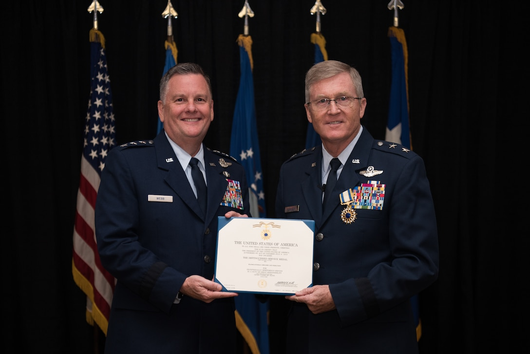 Lt. Gen. Marshall B. Webb (left), commander of the Air Force Special Operations Command (AFSOC), Hurlbert Field, Florida, presents the Distinguished Service Medal certificate to Maj. Gen. Gregory L. Ferguson, Air National Guard assistant to the commander, AFSOC, during Ferguson's retirement ceremony at Will Rogers Air National Guard Base in Oklahoma City, Aug. 4, 2018.