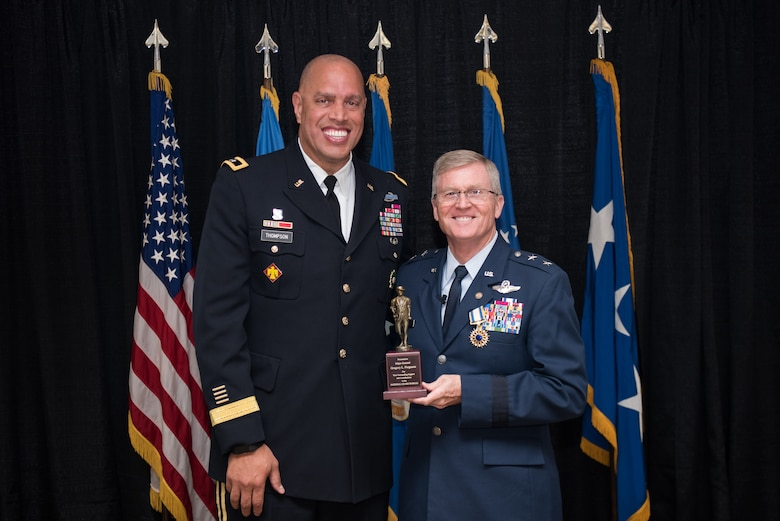 Maj. Gen. Michael C. Thompson (lfet), Oklahoma adjutant general, Joint Force Headquarter, Oklahoma City, presents a National Guard Bureau minuteman statue to Maj. Gen. Gregory L. Ferguson (right), Air National Guard assistant to the commander, Air Force Special Operations Command (AFSOC), Hurlbert Field, Florida, during Ferguson's retirement ceremony at Will Rogers Air National Guard Base in Oklahoma City, Aug. 4, 2018.
