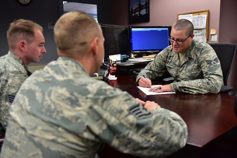 One man sits at a desk and signs a piece of paper, while two men sit on the other side of the desk and watch.