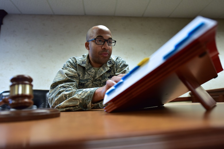 Man sits at desk and reads book.