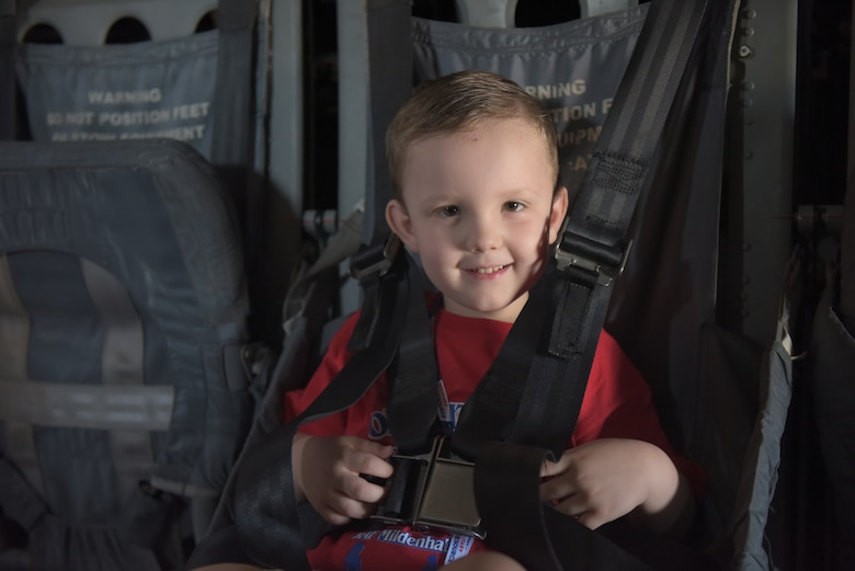"A boy is buckled into the seat of a CV-22 Osprey at RAF Mildenhall, England, Aug. 3, 2018. An MC-130J Commando and a KC-135 Stratotanker were also on display during the ""kids deployment line."" (U.S. Air Force photo by Senior Airman Kelly O'Connor)"