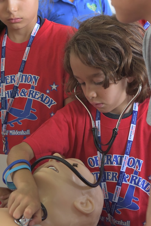 "A boy wears a stethoscope while learning how to listen to a heartbeat at RAF Mildenhall, England, Aug. 3, 2018. Self-aid and buddy care was one of the stations featured at the ""kids deployment line."" (U.S. Air Force photo by Senior Airman Kelly O'Connor)"