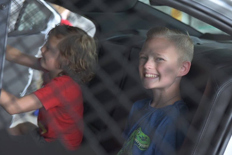 "A boy smiles in the back of a patrol car during the ""kids deployment line"" at RAF Mildenhall, England, Aug. 3, 2018. Security Forces was one of 22 agencies who participated in the event to teach kids what life is like while deployed. (U.S. Air Force photo by Senior Airman Kelly O'Connor)"