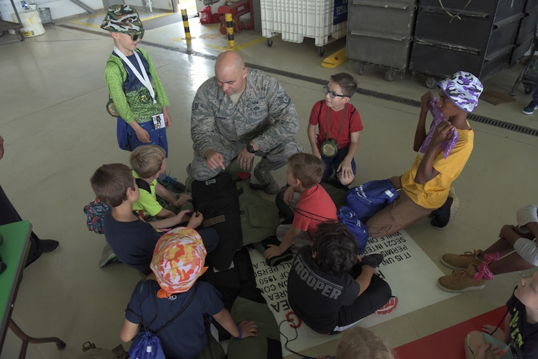 An Airman from the 48th Fighter Wing's Explosive Ordnance Disposal teaches kids about the protective body suit he wears for his job at RAF Mildenhall, England, Aug. 3, 2018. EOD was one of 22 agencies who participated in the event to teach kids what life is like while deployed. (U.S. Air Force photo by Senior Airman Kelly O'Connor)