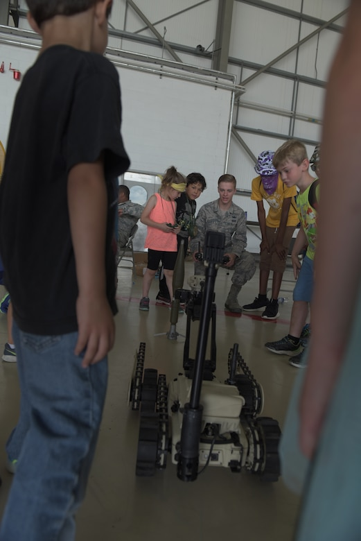 An Airman from the 48th Fighter Wing's Explosive Ordnance Disposal operates a robot as children look on at RAF Mildenhall, England, Aug. 3, 2018. EOD was one of 22 agencies who participated in the event to teach kids what life is like while deployed. (U.S. Air Force photo by Senior Airman Kelly O'Connor)