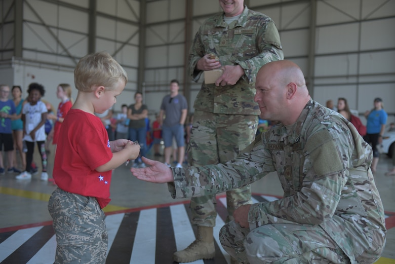 "A boy looks at the coin he received from his commander after completion of the ""kids deployment line"" at RAF Mildenhall, England, Aug. 3, 2018. The Airman and Family Readiness Center hosted the event for the second year in a row to teach kids about what life is like during a deployment. (U.S. Air Force photo by Senior Airman Kelly O'Connor)"