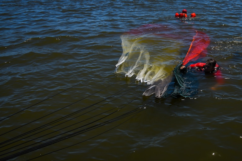 Master Sgt. Ben Domian, 308th Rescue Squadron survival, evasion, resistance and escape instructor, pulls a parachute during water survival training Aug. 4, 2018 at Patrick Air Force Base, Florida.