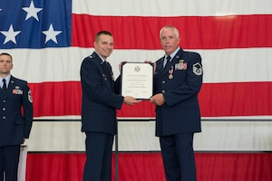 Master Sgt. Jeffrey Tompkins, 934th Maintenance Squadron, accepts his retirement certificate from Lt. Col. Andy Staut, 934th Maintenance Group deputy commander, Aug. 4. (Air Force Photo/Tech. Sgt. Amber E.N. Jacobs)
