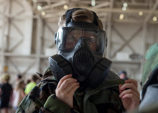 Mackenzie Buss, daughter of U.S. Air Force Maj. Mary Buss, an executive officer assigned to the 730th Air Mobility Training Squadron, wears mission-oriented protective posture gear during the Kids Deployment Line, August 2, 2018, at Altus Air Force Base, Okla.