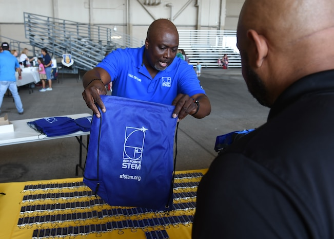 Nathan Covington, a school liaison officer at the Airman and Family Readiness Center, hands out a backpack for preschoolers at the Kids Deployment Line, August 2, 2018, at Altus Air Force Base, Okla.