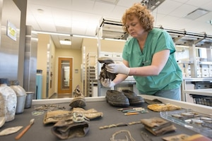 A lab worker examines personal effects that may have belonged to a fallen service member.