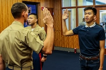 Staff Sgt. Jamescarlo Eco, staff noncommissioned officer in charge of Recruiting Substation Savannah, Recruiting Station Jacksonville, re-enlists as his brother, Marvic Eco, a poolee with RSS Jacksonville, enlists for the first time. The Eco brothers swore into the Marine Corps joined by their parents on July 26, 2018. (U.S. Marine Corps photo by Sgt. Tony Simmons)