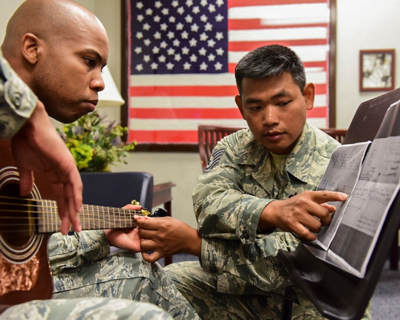 From left, U.S. Air Force Staff Sgt. Michael Burks, 1st Maintenance Squadron precision measurement equipment lab technician, and U.S. Air Force Tech. Sgt. Daniel Santos, U.S. Air Force Heritage Band of America guitarist, learn guitar chords at Joint Base Langley-Eustis, Virginia, July 31, 2018.