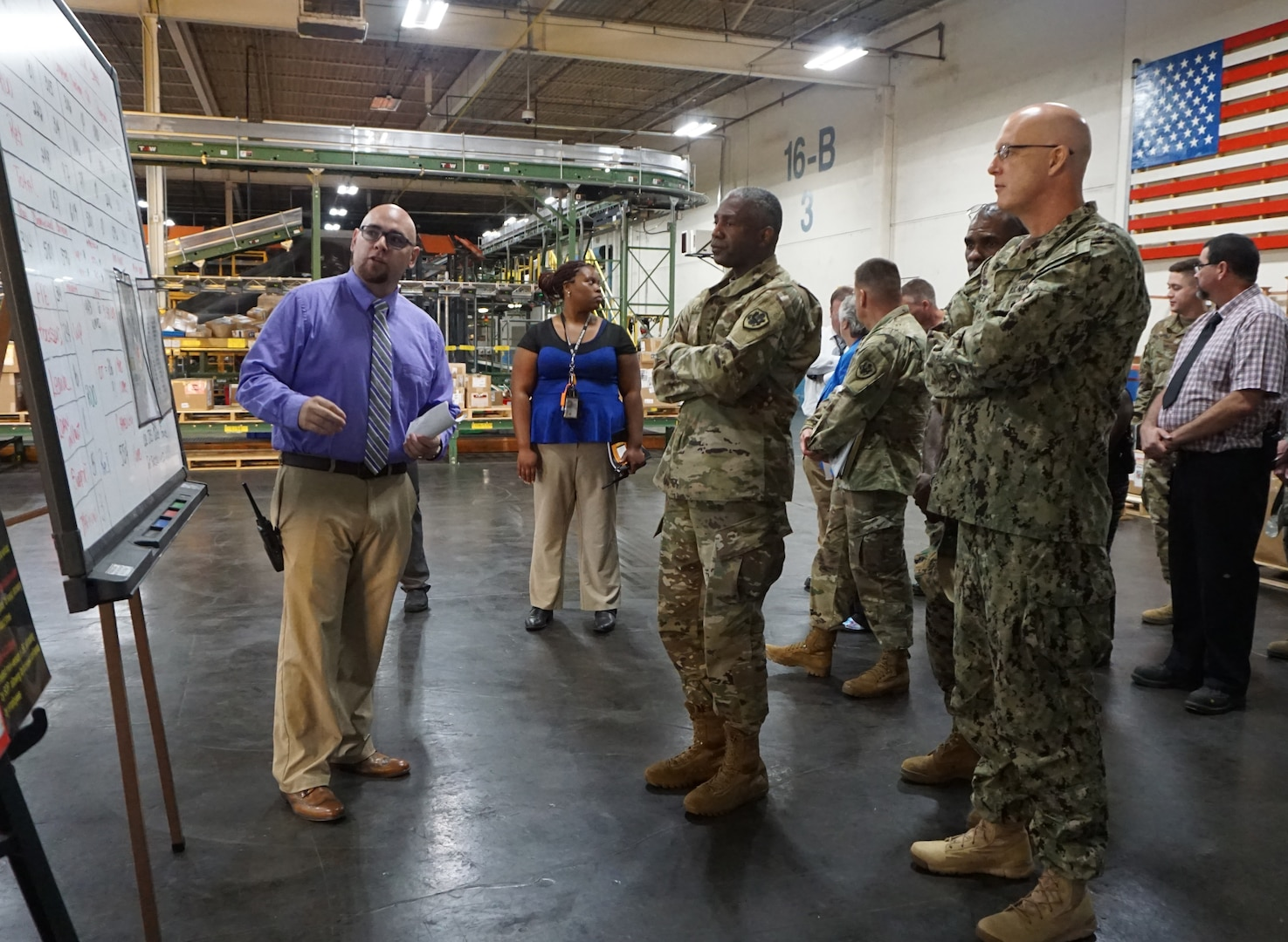 Marc Marquez, Bin Division Chief, is explaining the production board to the DLA Director as DLA Distribution Commanding Officer Navy Rear Adm. Kevin Jones and DLA Distribution San Joaquin Commander Marine Col. Andre Harrell listen.