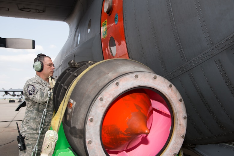 Master Sgt. Jeff Hardsock,302nd Aircraft Maintenance Squadron flight line expediter, inspects the U.S. Department of Agriculture Forest Service's Modular Airborne Fire Fighting System nozzle attached to an Air Force Reserve Command C-130 Hercules aircraft at Peterson Air Force Base, Colorado, Aug. 6, 2018.