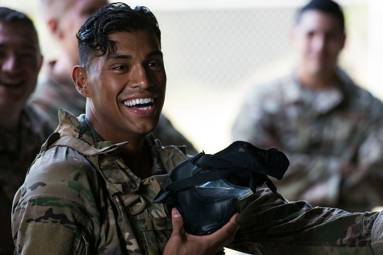 Tech. Sgt. Christopher Zavala, 822d Base Defense Squadron (BDS) squad leader, laughs before donning an M50 gas mask for the shooting competition portion of the Defender Challenge assessment, July 30, 2018, at Moody Air Force Base, Ga. Seven Moody defenders trudged through a gauntlet that tested their capability, lethality and readiness. Ultimately, only Senior Airman Jeffrey Lewis, 822d BDS fireteam leader, had the scores, determination and perseverance to advance to the next level for a chance to represent Air Combat Command during the 2018 Defender Challenge, Sept. 8-14, at Joint Base San Antonio-Camp Bullis, Texas. (U.S. Air Force photo by Airman 1st Class Erick Requadt)