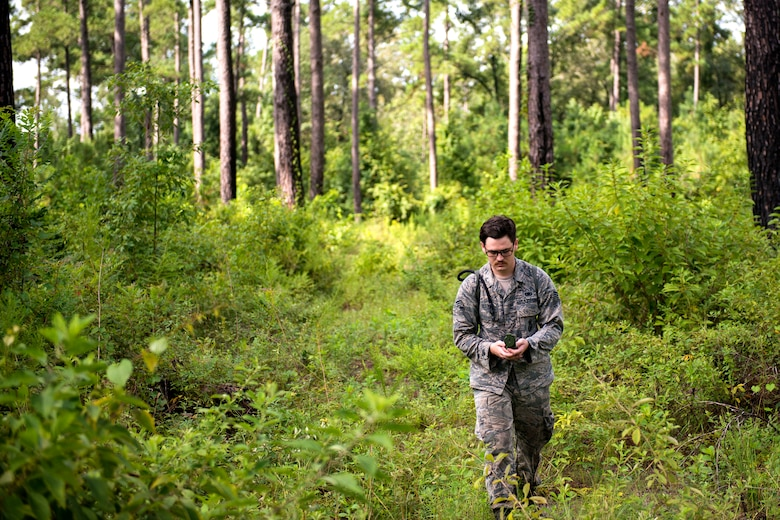Senior Airman Parker Bell, 23d Security Forces Squadron section patrolman, examines a compass during the land-navigation portion of the Defender Challenge assessment, July 30, 2018, at Moody Air Force Base, Ga. Seven Moody defenders trudged through a gauntlet that tested their capability, lethality and readiness. Ultimately, only Senior Airman Jeffrey Lewis, 822d Base Defense Squadron fireteam leader, had the scores, determination and perseverance to advance to the next level for a chance to represent Air Combat Command (ACC) during the 2018 Defender Challenge, Sept. 8-14, at Joint Base San Antonio-Camp Bullis, Texas. (U.S. Air Force photo by Airman 1st Class Erick Requadt)