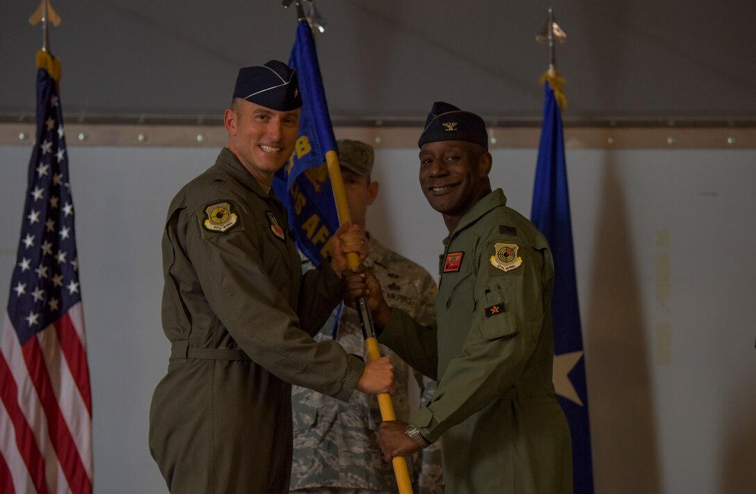 Brig. Gen. Robert Novotny, 57th Wing commander, passes the guidon to Col. Travolis Simmons, 57th Adversary Tactics Group incoming commander, during a change of command ceremony at Nellis Air Force Base, Nevada, Aug. 3, 2018. The 57th ATG is made up of seven squadrons, including three geographically separated units. (U.S. Air Force photo by Airman 1st Class Andrew D. Sarver)