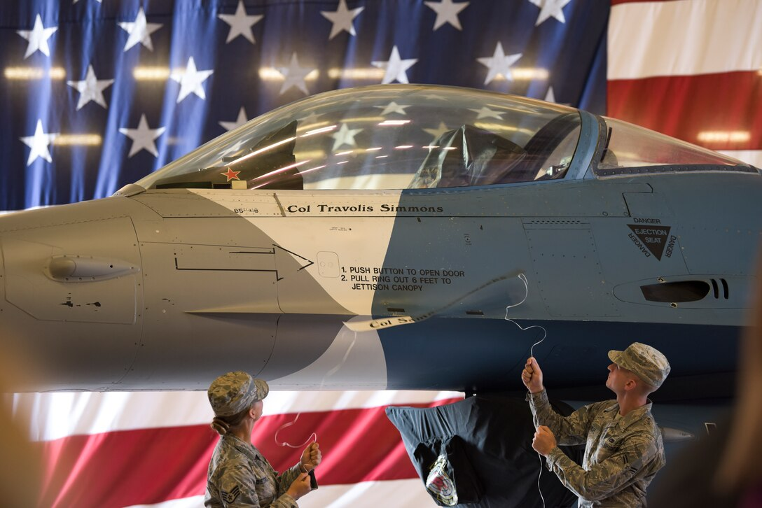 Airmen assigned to the 57th Aircraft Maintenance Squadron Viper Aircraft Maintenance Unit reveal the 57th Adversary Tactics Group incoming commander's name during a change of command ceremony at Nellis Air Force Base, Nevada, Aug. 8, 2018. The 57th ATG boasts the world's most capable and professional aggressor force to train US personnel and coalition partners during exercises and deployments. (U.S. Air Force photo by Airman 1st Class Andrew D. Sarver)