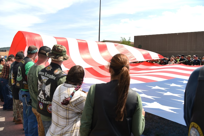 Participants from the Dakota Thunder Run fold a flag flown by retired Army 1st Sgt., Dana Bowman, a former Golden Knight parachute team member, as he parachuted to the ground at Sturgis, S.D., Aug. 7, 2018. Over 150 participants rode 53 miles from Ellsworth AFB to the Sturgis Motorcycle Rally, where they helped kick off Military Appreciation Day events. (U.S. Air Force photo by Airman 1st Class Thomas Karol)