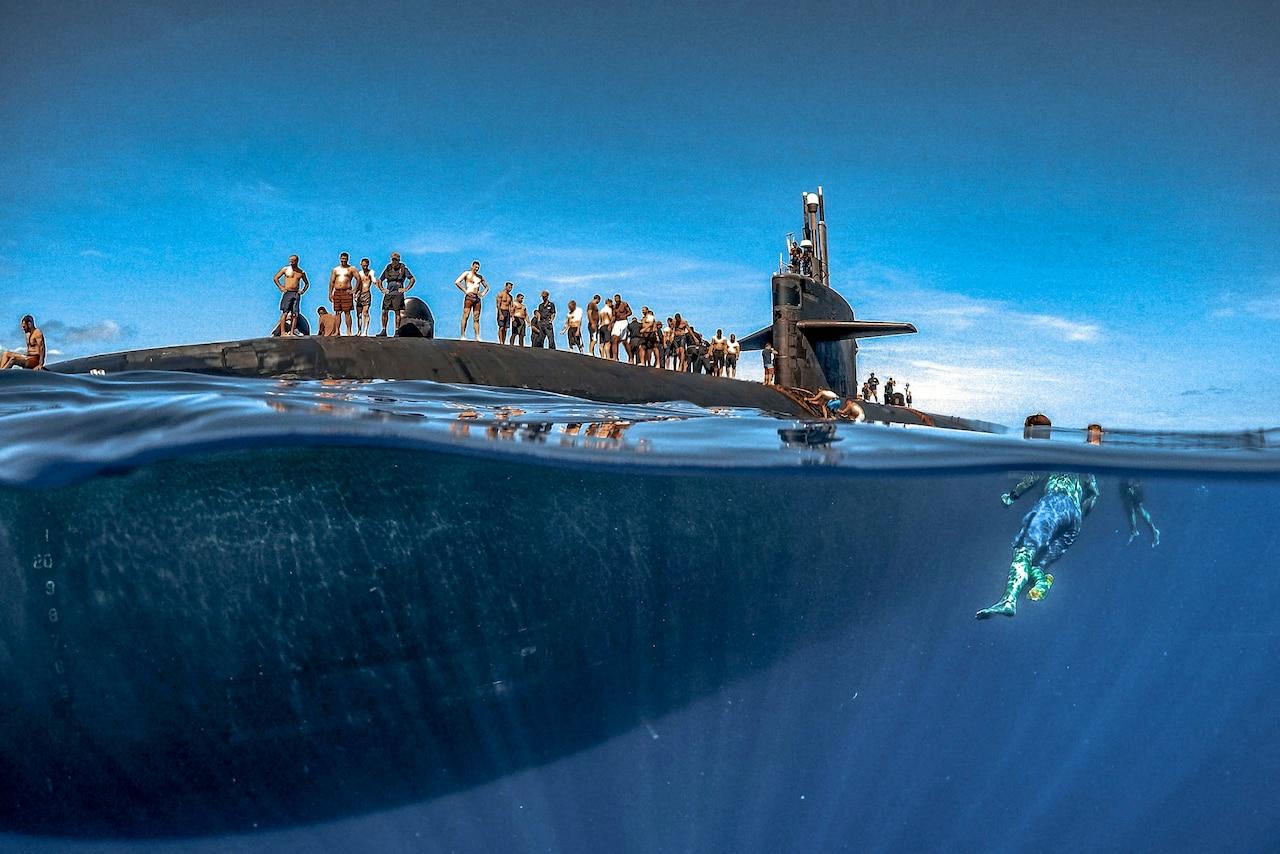 Sailors swim around a submarine.
