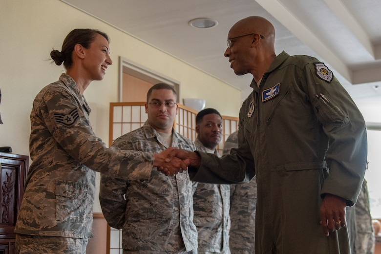 Gen. CQ Brown, Jr., Pacific Air Forces commander, presents a coin to Staff Sgt. Erika Wallfred   374th Communications Squadron, cyber systems defense supervisor, at Yokota Air Base, Japan, Aug. 8, 2018. This was Brown's first trip to the region since taking command on July 26, 2018.