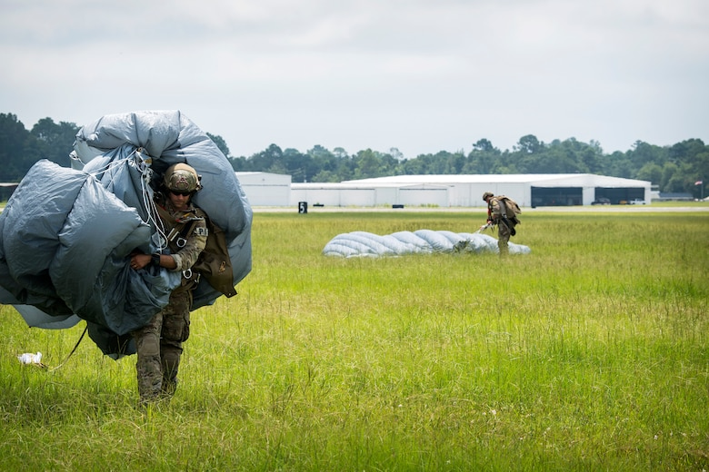 A Pararescueman (PJ) from the 38th Rescue Squadron (RQS), carries a parachute after a static-line jump, July 24, 2018, in Valdosta, Ga. PJs performed static-line jumps to maintain their jump proficiency qualifications. The mission of the 38th RQS is to employ combat ready rescue officers and pararescuemen to support units worldwide. (U.S. Air Force photo by Airman 1st Class Eugene Oliver)