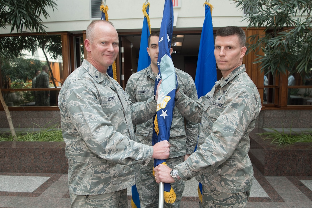 Brig. Gen. Michael Schmidt, left, Command, Control, Communications, Intelligence and Networks program executive officer, passes a guidon symbolizing Col. Jonathan Sorbet's assumption of leadership as the senior material leader for the Family of Advanced Beyond Line-of-Sight Terminals division within C3I&N August 8, at the MITRE Corp. in Bedford, Mass. (U.S. Air Force photo by Jerry Saslav)