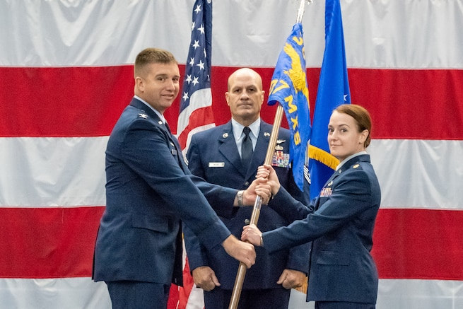 U.S. Air Force Col. Casey Cooley, 307th Maintenance Group commander, hands the 707th Maintenance Squadron guidon to the unit's new commander Maj. Jessica Oberlander, during the unit's change of command ceremony at Barksdale Air Force Base, Louisiana, August 5, 2018.   Oberlander comes to the unit from Headquarters, U.S. Air Force in Washington D.C. where she served as the chief for Global Power Product Support Integration and Oversight. (U.S. Air Force photo by Tech. Sgt. Cody Burt)