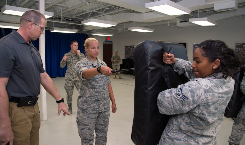 U.S. Air Force Airman 1st Class Casey Atanasio, center, a patient travel coordinator assigned to the 6th Medical Support Squadron, learns proper distance and form for baton strikes at MacDill Air Force Base, Fla., July 25, 2018.