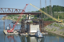 A tow boat pulls out a barge after a gantry crane picked up a 1.3 million pound concrete shell Aug. 3, 2018 downstream of Kentucky Lock in Grand Rivers, Ky. The U.S. Army Corps of Engineers Nashville District and contractor, Johnson Brothers, were preparing to place it on the riverbed where it will be part of a coffer dam and eventually a permanent part of the new lock wall for the Kentucky Lock Addition Project. An issue with the strand jack delayed the placement of the concrete shell until Aug. 6. It is the first of 10 shells being placed over the next year. The lock is located at Kentucky Dam, which is a Tennessee Valley Authority project at Tennessee River mile 22.4. (USACE Photo by Lee Roberts)