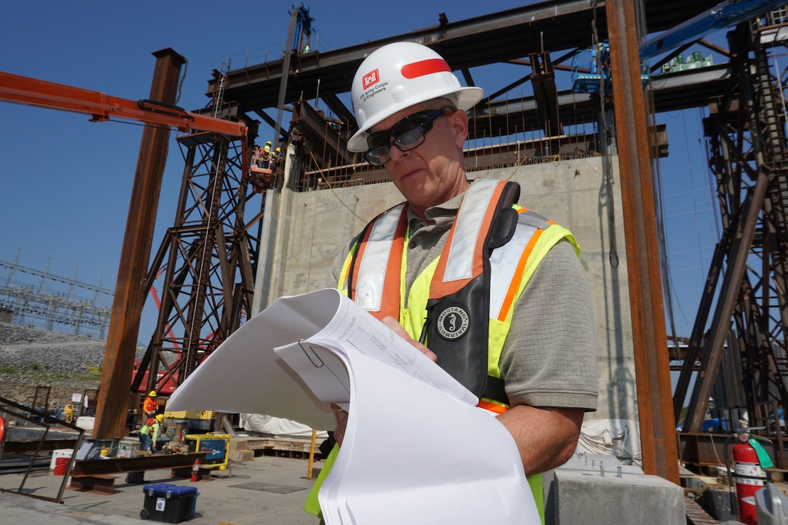 Barney Schulte, technical engineer for Kentucky Lock Addition Project, checks specifications for the gantry crane lift system in preparation for the movement of a 1.3 million pound concrete shell Aug. 4, 2018 into the downstream riverbed to form a cofferdam.  The shell will also be part of the permanent lock wall. (USACE Photo/Mark Rankin)