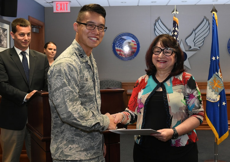 Capt. Taeyoung Lee, a program manager under Battle Management, accepts a certificate of completion from Catherine Kendrick, dean of the Division of Online and Continuing Education at the University of Massachusetts Lowell, during a program manager seminar graduation ceremony at Hanscom Air Force Base, Mass. Aug. 8.