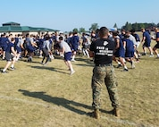 Gunnery Sgt. Joseph Ferguson, the logistics chief of Marine Corps Recruiting Station Twin Cities, leads a Leadership and Cohesion Exercise physical training event with 100 student athletes from the Concordia University football team, 8 August, 2018, at Camp Ripley in Little Falls, Minn. The exercise, led by the Minneapolis Officer Selection Team, challenged the players to push themselves past their comfort zone and taught them about the leadership ethos engrained within the Marine Corps while helping them to grow stronger as a team. (Courtesy photo)