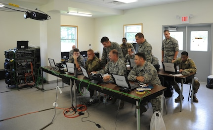 Airmen and Soldiers gather during Exercise Patriot Warrior for cyber defense training on Aug. 8, 2018, at Fort McCoy, Wisc. Patriot Warrior is Air Force Reserve Command's premier exercise, providing an opportunity for Reserve Citizen-Airmen to train with joint partners in the combat support training exercise.