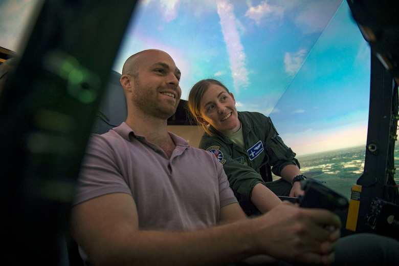 1st Lt. Laney Schol, right, 74th Fighter Squadron A-10C Thunderbolt II pilot, instructs Gavin Harnett, RAND associate physical scientist, as he flies in an A-10 simulator, Aug. 8, 2018, at Moody Air Force Base, Ga. RAND integrated with Moody's rescue, flying and maintenance professionals to examine firsthand Air Force operations. This familiarization helps RAND develop their analysis to ultimately present policy recommendations to Air Force decision makers. Since 1948, RAND has performed analysis for the U.S. Air Force. (U.S. Air Force photo by Senior Airman Greg Nash)