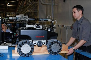 A Navy engineer raises a robot onto blocks.