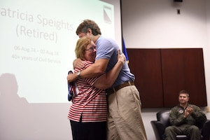 Patricia Speights, former 14th Operations Group secretary, hugs her son, Jamie, after presenting him with an American flag Aug. 3, 2018, on Columbus Air Force Base, Mississippi. Speights and her family served the Air Force for 40 years. (U.S. Air Force photo by Airman 1st Class Beaux Hebert)
