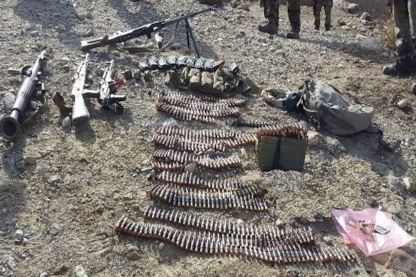 A stockpile of ISIS-K weapons are spread out on the ground in Afghanistan.