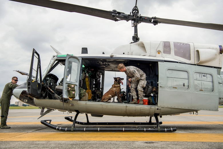 Staff Sgt. Cody Nickell, 374th Security Forces Squadron military working dog handler, works with Topa, 374th SFS MWD, to get him accustomed to being inside a UH-1N helicopter during a 459th Airlift Squadron MWD familiarization flight July 26, 2018, at Yokota Air Base, Japan. Flying in a helicopter can be hard for the MWD's due to the noise and vibrations, but once the MWDs become comfortable with the aircraft, they can be transported quickly and efficiently to wherever needed. (U.S. Air Force photo by Senior Airman Donald Hudson)