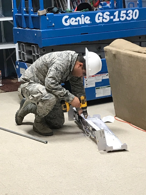 An Airman from the 49th Civil Engineer Squadron repairs a light fixture during the renovation of building 232. (Courtesy photo)