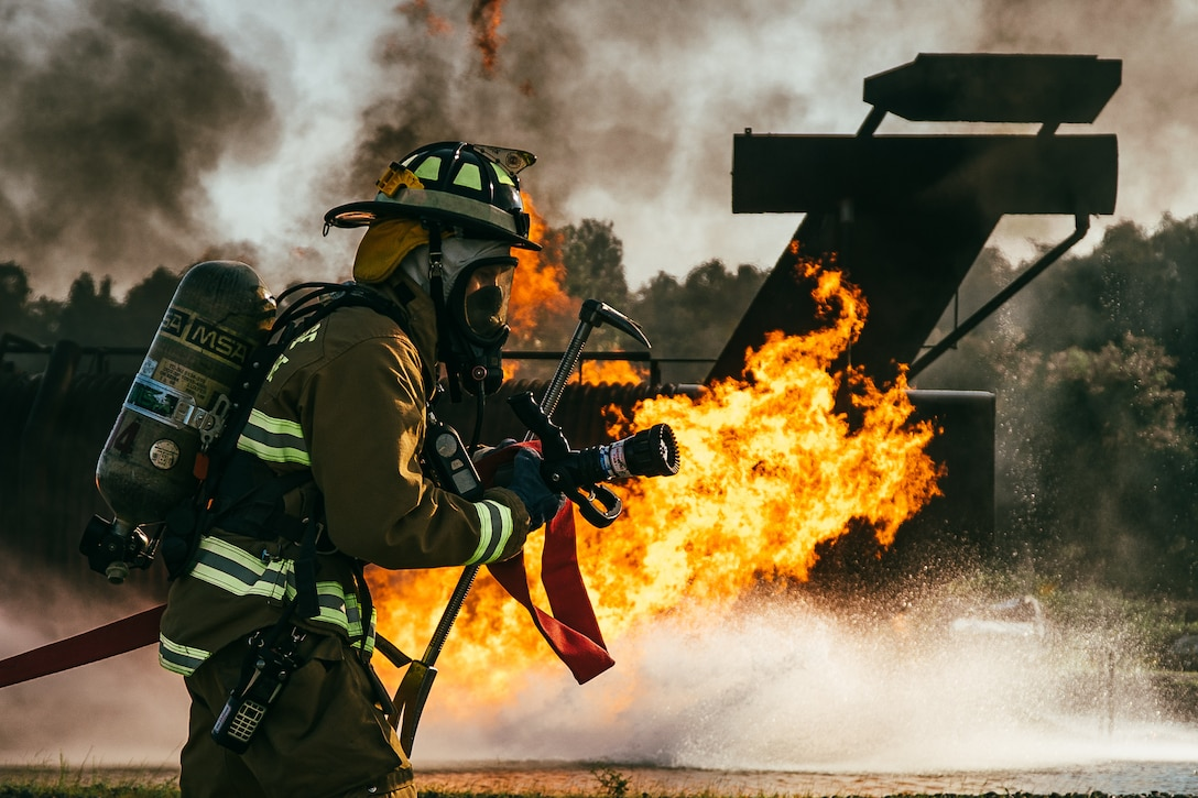 Senior Airman William Leuzinger, 11th Civil Engineer Squadron fire and emergency services firefighter, pulls a fire hose toward a simulated aircraft fire during a training exercise at Joint Base Andrews, Md., Aug. 9, 2018. During the training, firefighters were split into three teams of two, with two teams extinguishing fires and the remaining team on standby. (U.S. Air Force photo by Staff Sgt. Delano Scott)