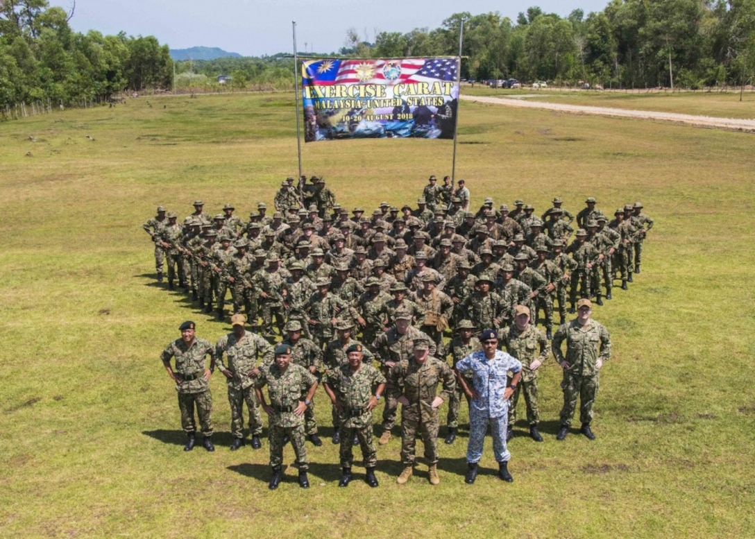 U.S. Marines stand in formation with Marines from the Royal Malaysian Navy for a photo during the opening ceremony of Cooperation Afloat Readiness and Training on Kota Belud Marine Base, Malaysia.