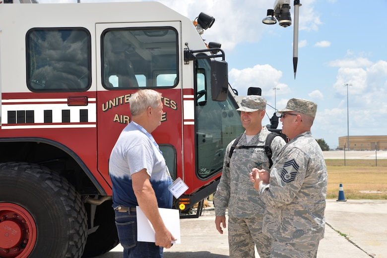 Dale Johnson, DLJ Commercial Roofing owner, talks with Master Sgt. Stephen M. Johnson, 433rd Civil Engineering Squadron assistant fire chief, and Chief Master Sgt. Robert M. Clarkin, 433rd Civil Engineering Squadron fire chief, about firefighting with an Oshkosh Striker aircraft rescue and firefighting vehicle at Joint Base San Antonio-Lackland, Texas Aug. 4, 2018. (U.S. Air Force photo by Master Sgt. Kristian Carter