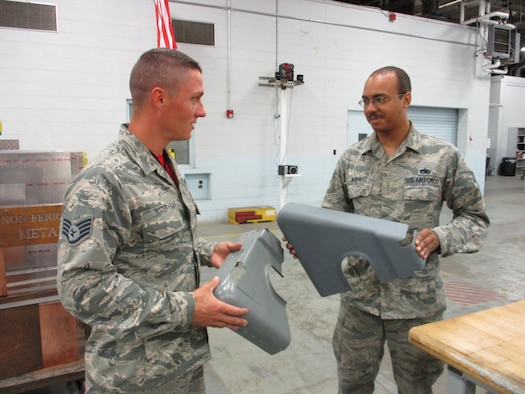 Staff Sgt. Christopher Ritter, 513th Maintenance Squadron Section Chief, and Staff Sgt. Michael Wright, 552nd Maintenance Squadron Aircraft Metals Technology, discuss the differences 3-D printing bring to the AWACS fabrications shop.  The damaged part has a two-year backlog for replacement parts and requires riveted reinforcement, while the printed part has reinforcements belt in  and can be printed in a single day. (U.S. Air Force photo by Master Sgt. Andrew Stephens)