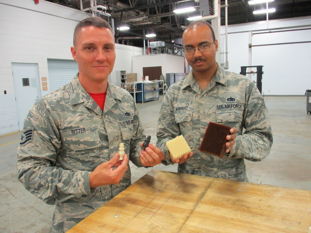 Staff Sgt. Christopher Ritter, 513th Maintenance Squadron Section Chief, and Staff Sgt. Michael Wright, 552nd Maintenance Squadron Aircraft Metals Technology, show the difference between 3-D printed parts and manufactured parts.  Whether printing up something as simple as a plastic seat handle or as complex as a replacement for phenolic resin honeycomb, 3-D printing saves Tinker AFB's Team AWACS time and money while improving aircraft readiness. (U.S. Air Force photo by Master Sgt. Andrew Stephens)