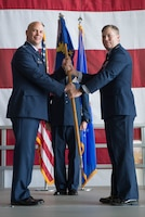U.S. Air Force Col. Michael Manion, 55th Wing commander, left, presents accepts the guidon of the 55th Maintenance Group (MXG) to from U.S. Air Force Col. Clayton Seale, the outgoing 55th MXG commander, during a change of command ceremony July 25, 2018, at Offutt Air Force Base (AFB), Nebraska. Seale led 1,200 personnel responsible for providing maintenance to 33 aircraft and all transient aircraft equipment for Offutt AFB. (U.S. Air Force photo by Zachary Hada)