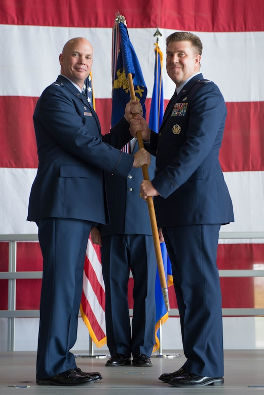 U.S. Air Force Col. Michael Manion, 55th Wing commander, left, presents the guidon of the 55th Maintenance Group (MXG) to U.S. Air Force Col. Todd Hammond, the incoming 55th MXG commander, during a change of command ceremony July 25, 2018, at Offutt Air Force Base (AFB), Nebraska. The 55th MXG has operational control of three squadrons and provides centralized direction of all maintenance staff functions for Offutt AFB. (U.S. Air Force photo by Zachary Hada)