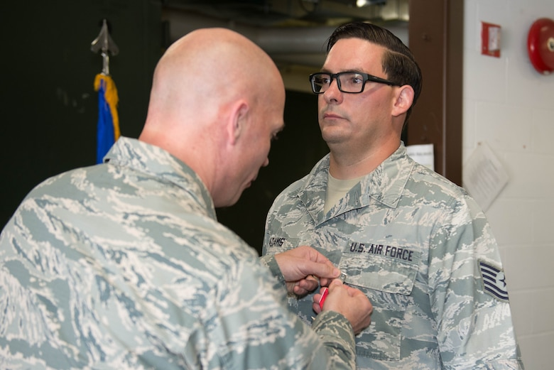 U.S. Air Force Col. Michael Manion, 55th Wing commander, pins a Bronze Star Medal to Tech. Sgt. William Adams, 55th Strategic Communications Squadron tactical radio supervisor, Aug. 7, 2018, at Offutt Air Force Base, Nebraska. Adams was awarded the Bronze Star Medal for meritorious achievement during a yearlong deployment at Kandahar Airfield, Afghanistan. (U.S. Air Force photo by Zachary Hada)